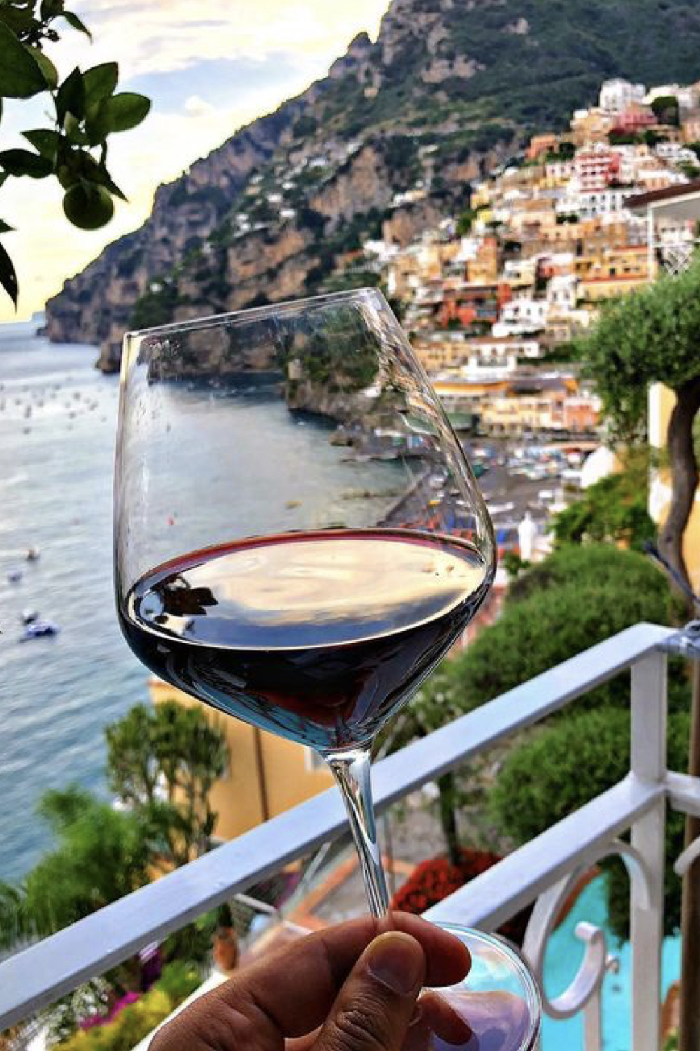 Person holding up a glass of red wine