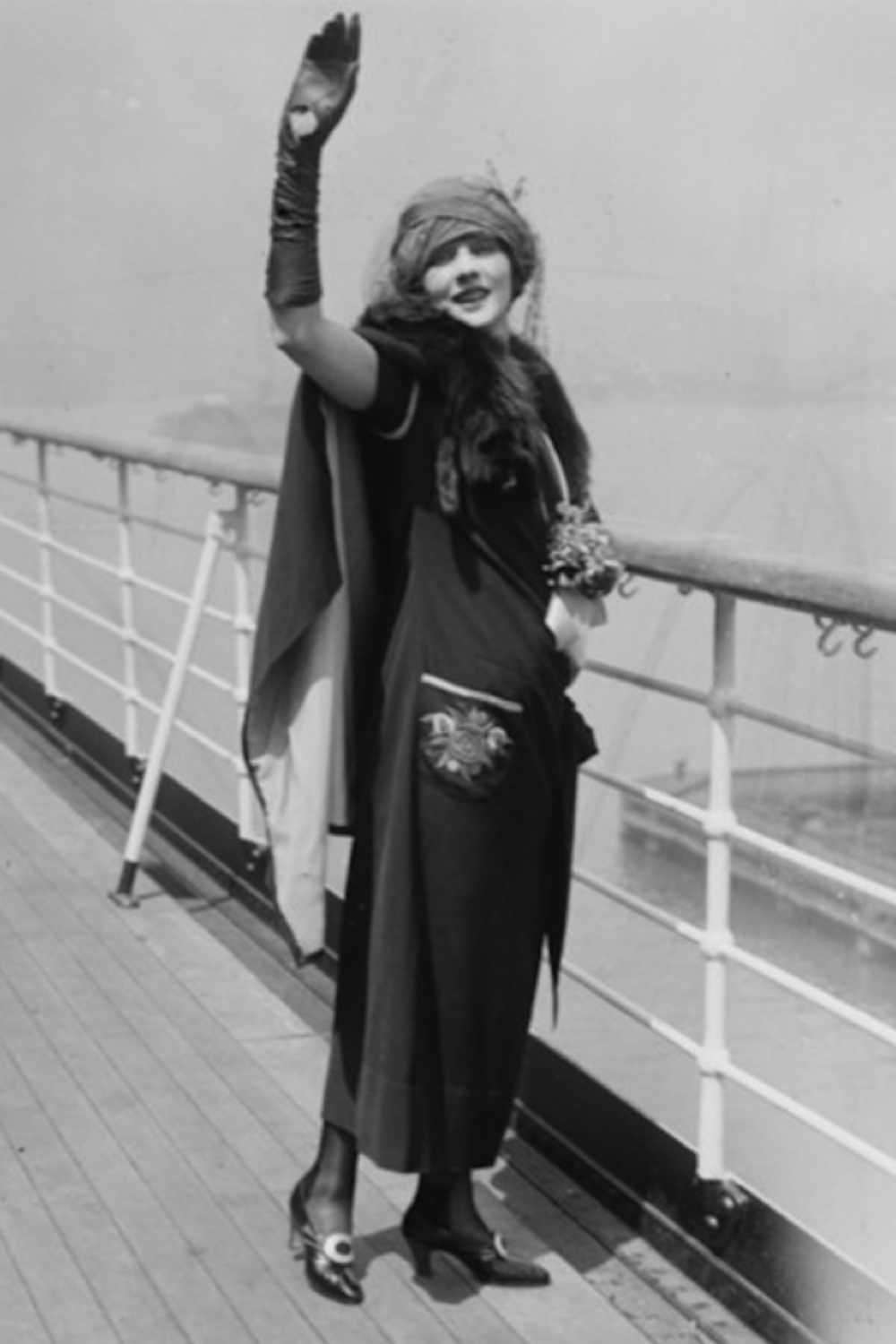Old Timey photo of a woman standing on a bridge waving